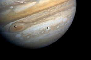 moons Io and Europa with Jupiter's Great Red Spot behind them